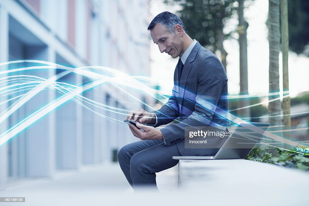 Waves of blue light and businessman texting on smartphone : Stock Photo