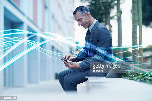 Waves of blue light and businessman texting on smartphone
