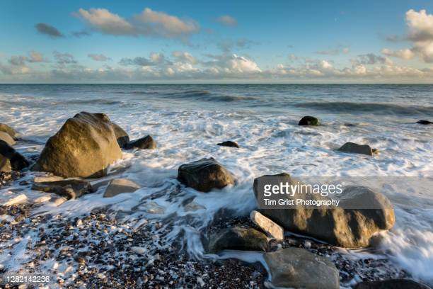 waves on a rocky beach at sunset - tide stock pictures, royalty-free photos & images