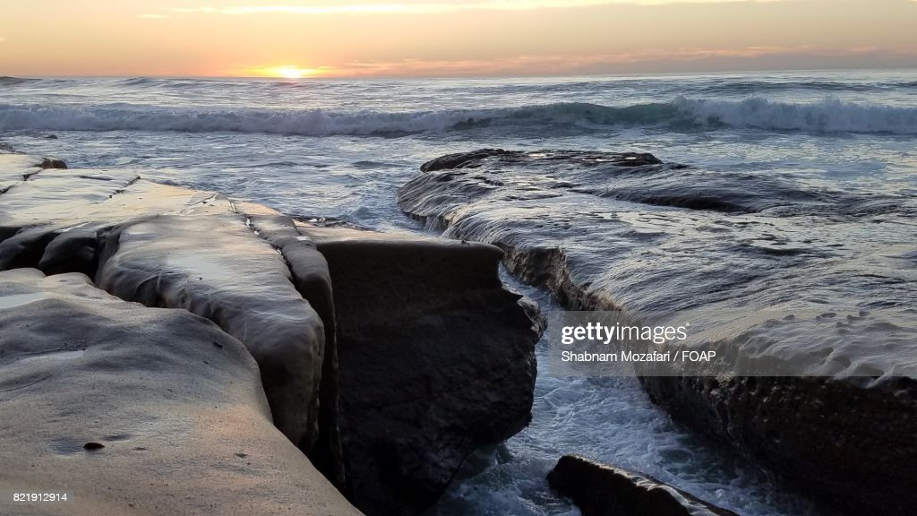 Waves on rocks at sunset : Stock Photo