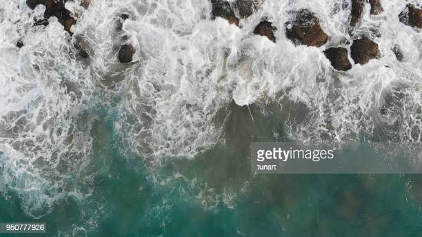 waves over rocky sea - rock stock pictures, royalty-free photos & images
