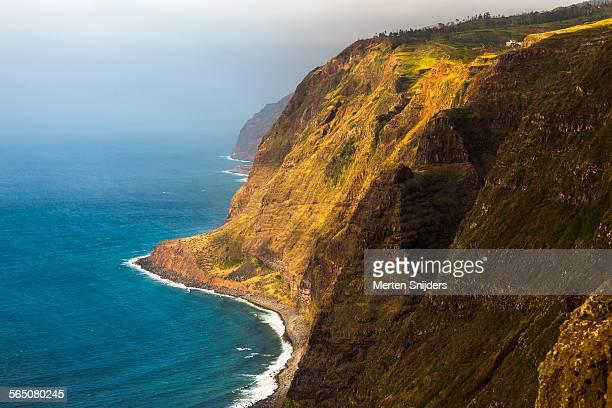 waves rolling in below steep precipice - merten snijders stockfoto's en -beelden