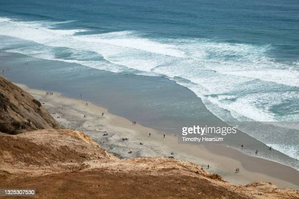 waves rolling in; cliff in foreground; distant view of people on a beach below - timothy hearsum stock-fotos und bilder