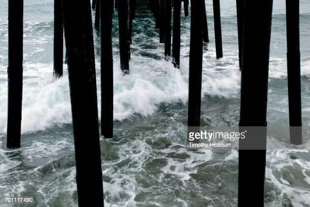 waves rush under pilings for a pier - timothy hearsum stockfoto's en -beelden