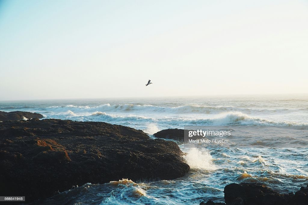 Waves Rushing At Rocks Against Clear Sky : Stock Photo