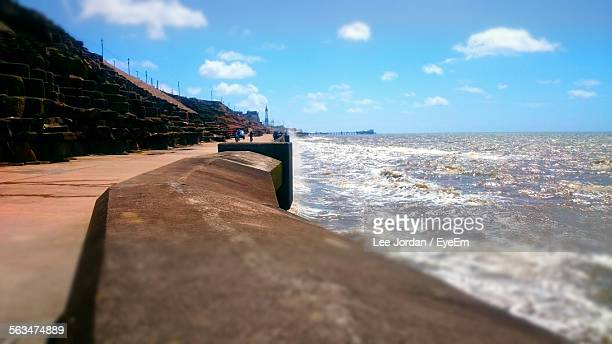 Waves Rushing Towards Retaining Wall Against Blue Sky