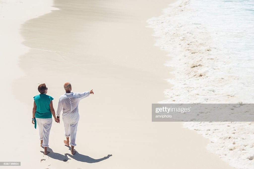 waves sand beach senior couple walking : Stock Photo