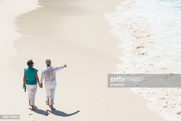 waves sand beach senior couple walking