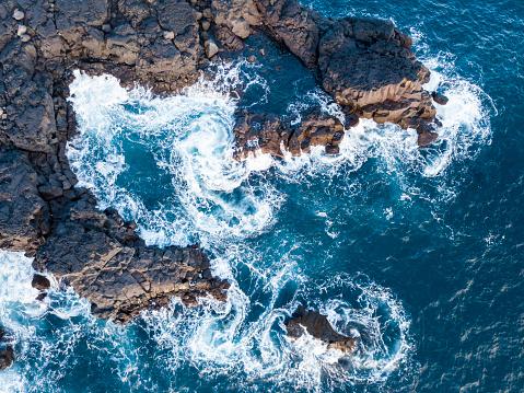 Waves splashing against volcanic rocks 865016798