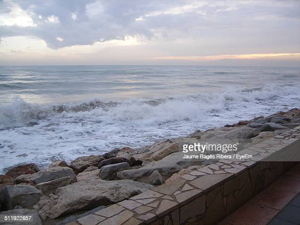 Waves splashing at rocky shore against cloudy sky