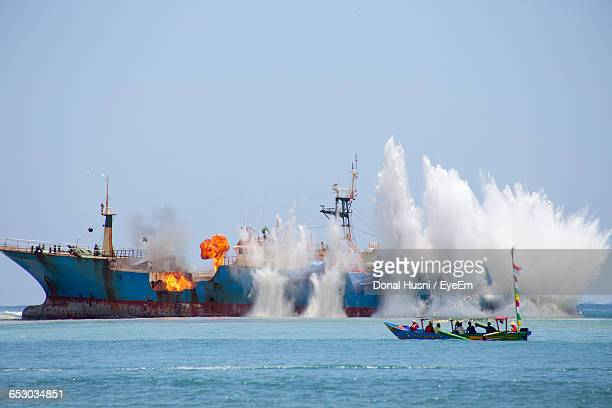 Waves Splashing On Burning Ship In Sea Against Clear Sky