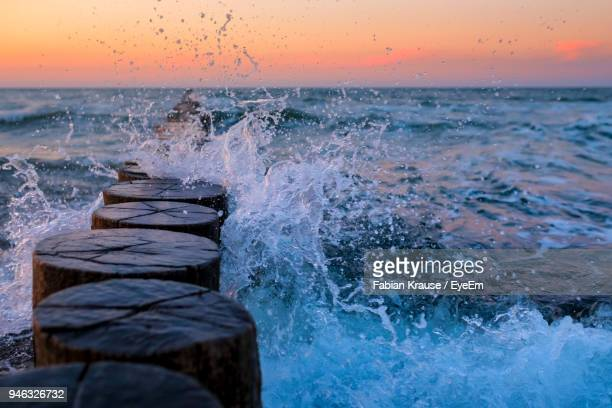 Waves Splashing On Groyne At Shore Against Sky During Sunset