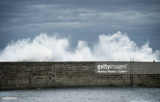 Waves Splashing On Retaining Wall Against Cloudy Sky