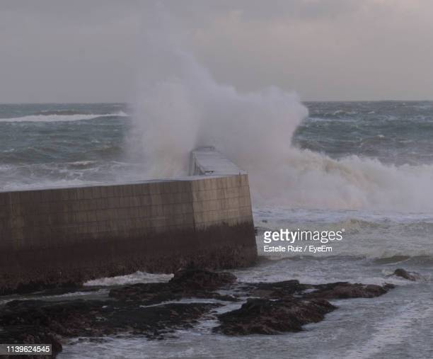 waves splashing on retaining wall against sky - retaining wall stock pictures, royalty-free photos & images
