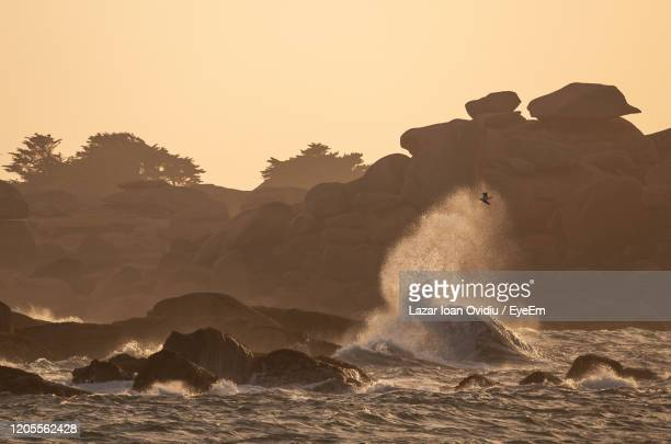 waves splashing on rocks at shore against clear sky - france strike stock pictures, royalty-free photos & images