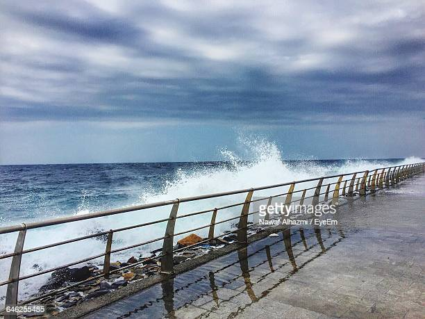 waves splashing on rocks by bridge against cloudy sky - jiddah stock pictures, royalty-free photos & images