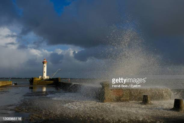 waves splashing on shore against sky - france strike stock pictures, royalty-free photos & images