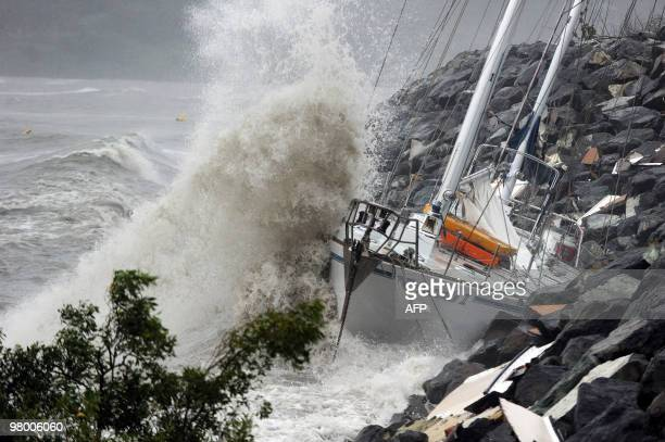 Waves stirred up by Cyclone Ului batter former Sydney to Hobart race yacht 'Anaconda II' against the seawall at Airlie Beach along the Queensland...