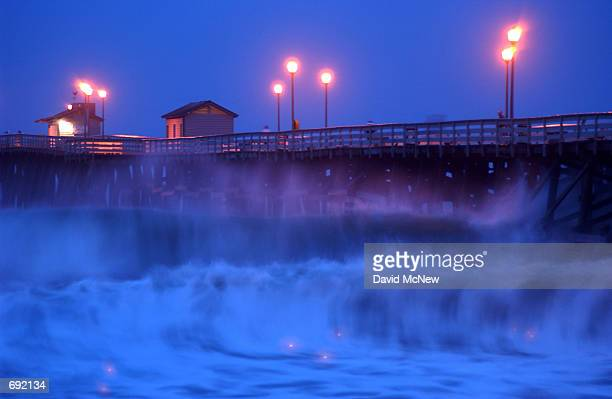 Waves up to 12 feet shake the San Clemente pier shortly after a pre-dawn astonomical high tide, January 9 in San Clemente, CA. A Pacific storm...