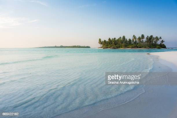 Waves wash over sandy beach on a tropical island at late afternoon