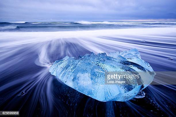Waves washing around a small iceberg on the beach at Jokulsarlon in Iceland Jokulsarlon Iceland