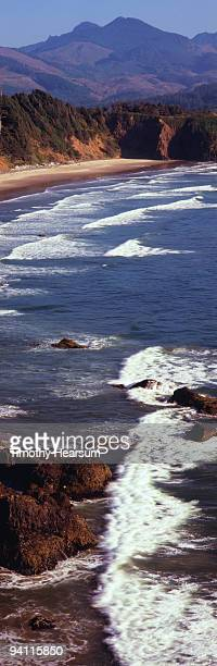 waves washing ashore,  beach and mountains beyond - timothy hearsum stock photos and pictures