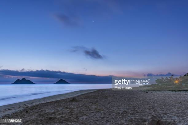 waves washing up on tropical beach at twilight, kailua, hawaii, united states - tranquil scene stock pictures, royalty-free photos & images