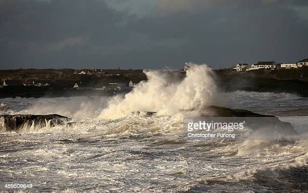 Waves whipped up by the wind crash against rocks at Trearddur Bay on December 27, 2013 in Anglesey, United Kingdom. A yellow 'be aware' warning has...