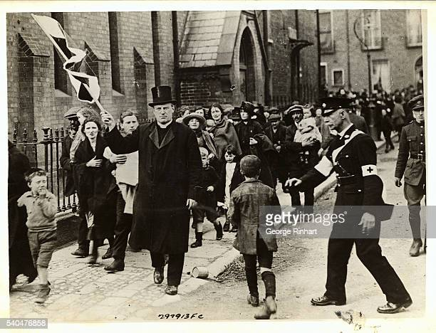 Waving a Red Cross fkag the Reverend Father O'Reilly is seen leading Dublin poor folk to safety from the War Zones of that troubled city during the...