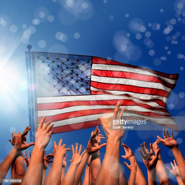 waving American flag and group of hands in air over sunny sky