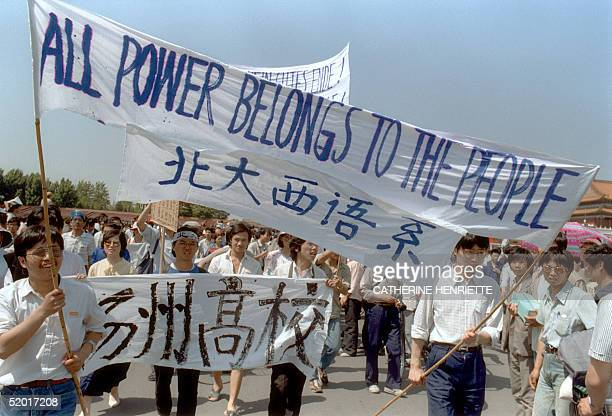 Waving banners high school students march in Beijing streets near Tiananmen Square 25 May 1989 during a rally to support the prodemocracy protest...