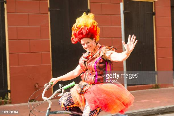 waving costumed woman bikes french quarter new orleans mardi gras - new orleans mardi gras stock photos and pictures