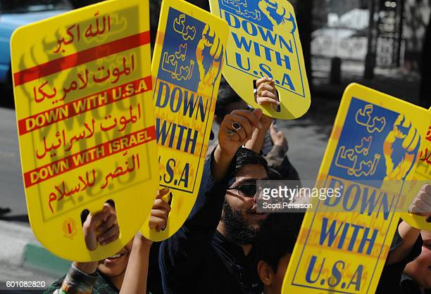 Waving 'Down with USA' placards Iranians held an antiSaudi Arabia street rally to mark the oneyear anniversary of more than 460 Iranians being killed...
