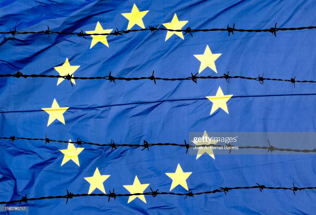 Waving European Union flag and barbed wire. : Stock Photo