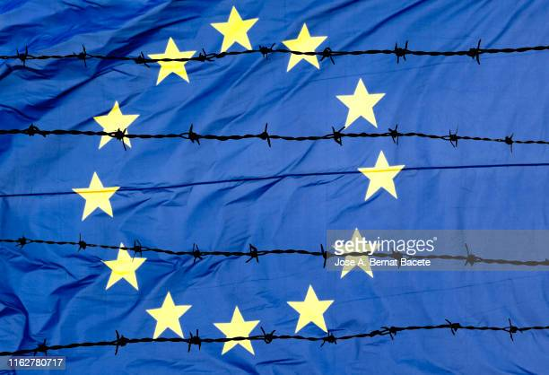 waving european union flag and barbed wire. - flyktingläger bildbanksfoton och bilder