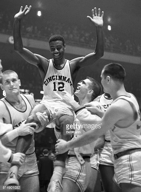 Waving his arms in jubilation Cincinnati basketball ace Oscar Robertson is carried on the shoulders of joyful teammates after landing his team to the...