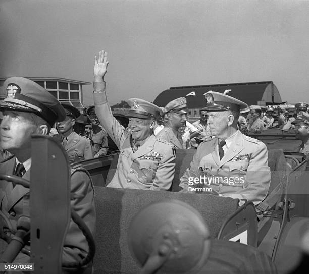 Waving his hand and wearing the famous Esienhower grin the nation's number one hero General of the Army Dwight D Eisenhower acknowledges the cheers...