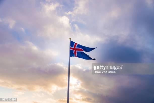 Waving Icelandic flag against cloudy sky.