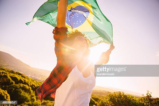waving the brazilian flag - brazil stock pictures, royalty-free photos & images