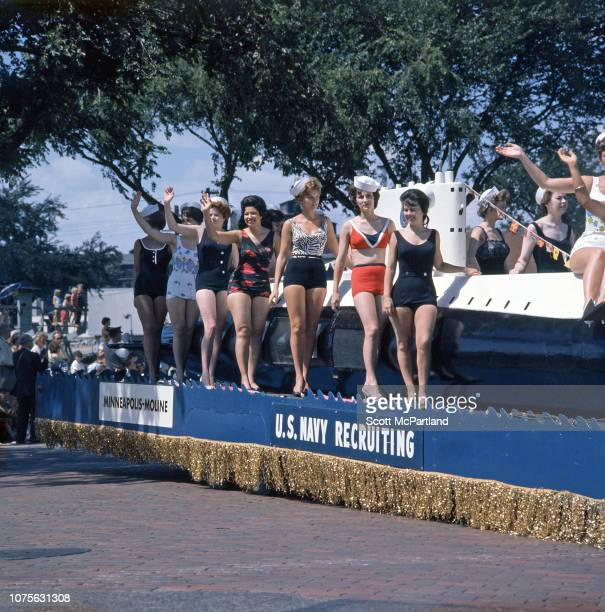 Waving to spectators women dressed in bathing suits ride a US Navy Recruiting parade float that features a scale model of a submarine during the...