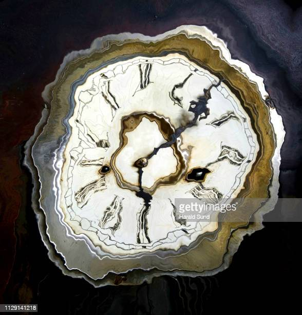 Wavy distorted appearing vintage antique grandfather clock face with Roman numeral numbers and hour and second hands.