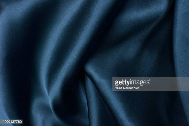 wavy folds of grunge blue silk texture satin velvet material or luxurious blue silk as background, folds of blue silky fabric. - vestido azul fotografías e imágenes de stock