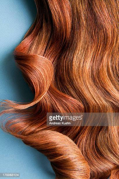 wavy red hair on a blue background. - wavy hair stock pictures, royalty-free photos & images