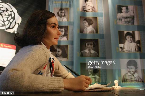 A wax figure of Anne Frank stands on display in front of pictures of the real Anne Frank as a child on its first public day at Madame Tussauds on...