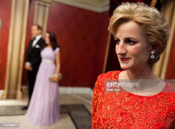 A wax figure of Lady Diana looks on as new wax figures of Prince William Duke of Cambridge and Catherine Duchess of Cambridge are unveiled at Madame...