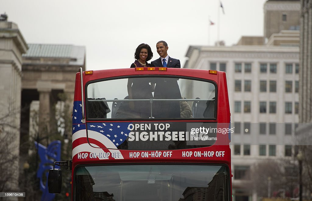 Wax figures of President Barack Obama and First Lady Michelle Obama ride in an open top bus down F Street, NW, en route to a display at Madame Tussauds wax museum.