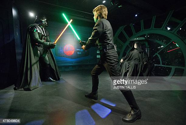 Wax figures of Star Wars characters Luke Sykwalker and Darth Vader fight under the eyes of Emperor Palpatine at the Star Wars At Madame Tussauds...