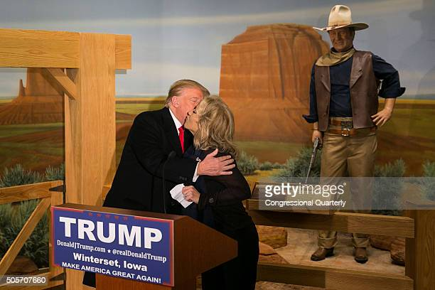 Wax statue of John Wayne watches as Republican presidential candidate Donald Trump kisses John Wayne's daughter, Aissa, during a news conference at...