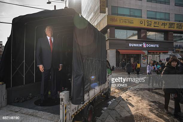 A waxwork figure of US Presidentelect Donald Trump is prepared to be placed on a street after it was unveilied at the Grevin waxwork museum in Seoul...