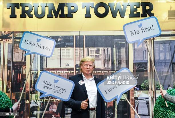 Waxwork model of US President Donald Trump is framed by famous tweets comments in front of a picture of the New-York Trump Tower at Madame Tussaud's...